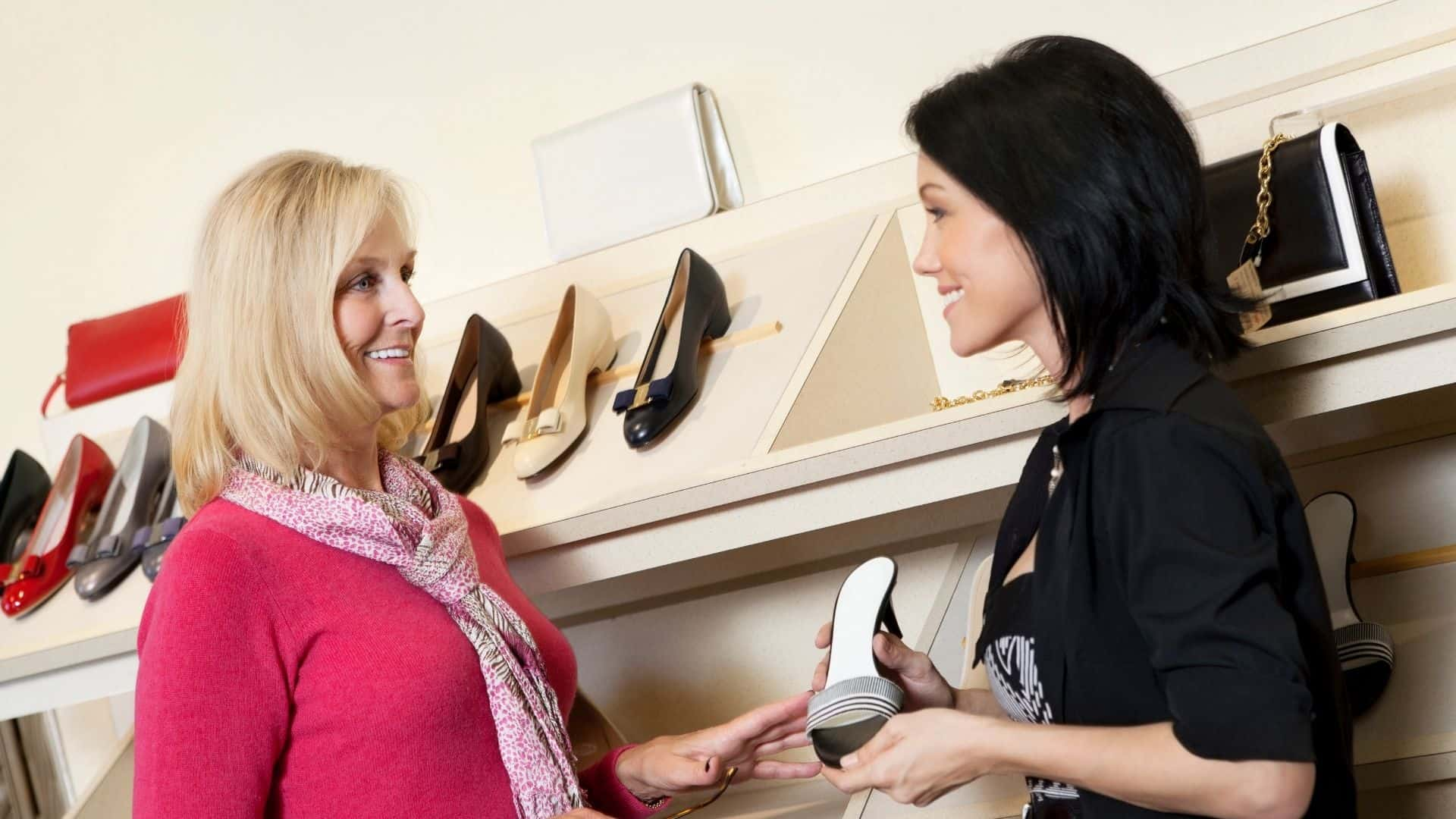 sales person talking to a customer holding a pair of shoes