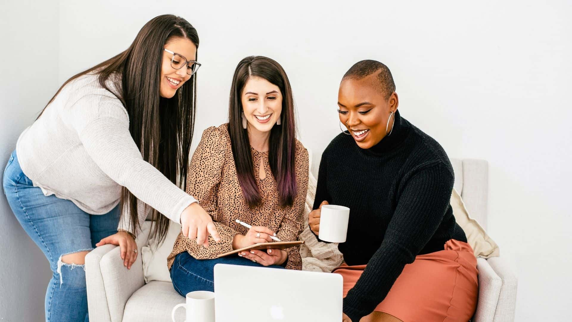 three business woman looking at a laptop