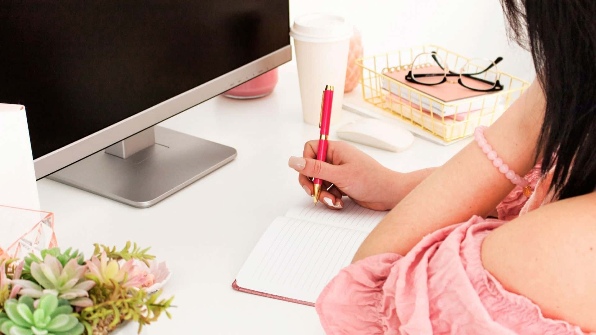 business woman taking some downtime and journaling at her desk